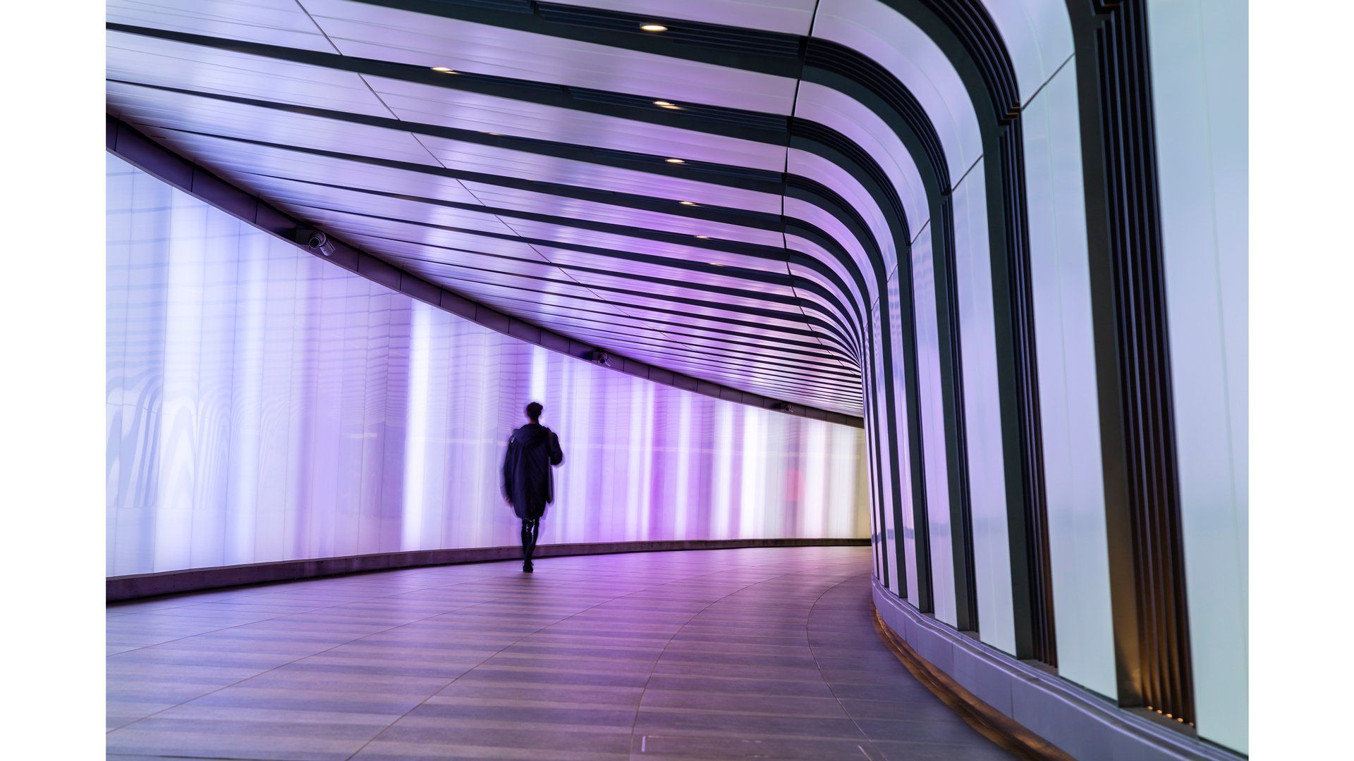 A person walks through a wide white and black tunnel with a purple light.